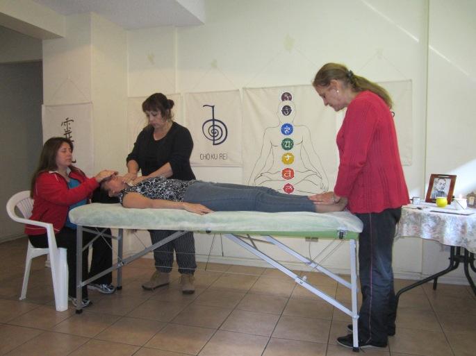 Carolina Cabeazas, Sandra Carrasco y María Soledad Portell entregando Reiki a Maribel López